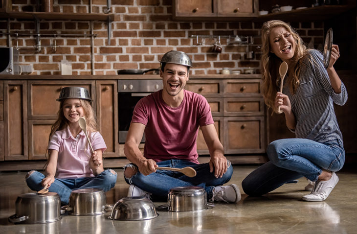 Family playing band with dishes on kitchen floor