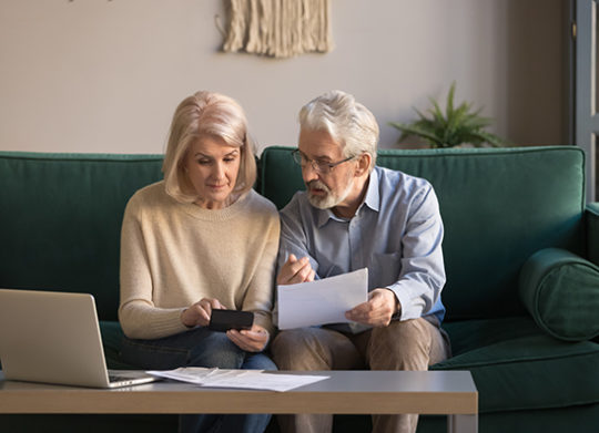 My Investment_ iew Older couple Looking at finances on Laptop