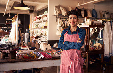 business woman smiling in front of her shop