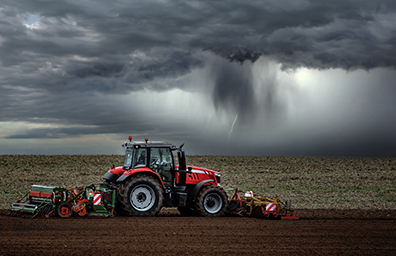 farm tractor working before rain storm