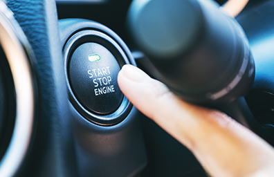 finger pushing the start button on new car