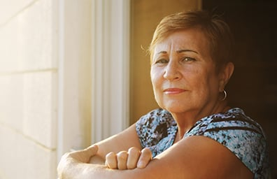 older hispanic female looking out her window