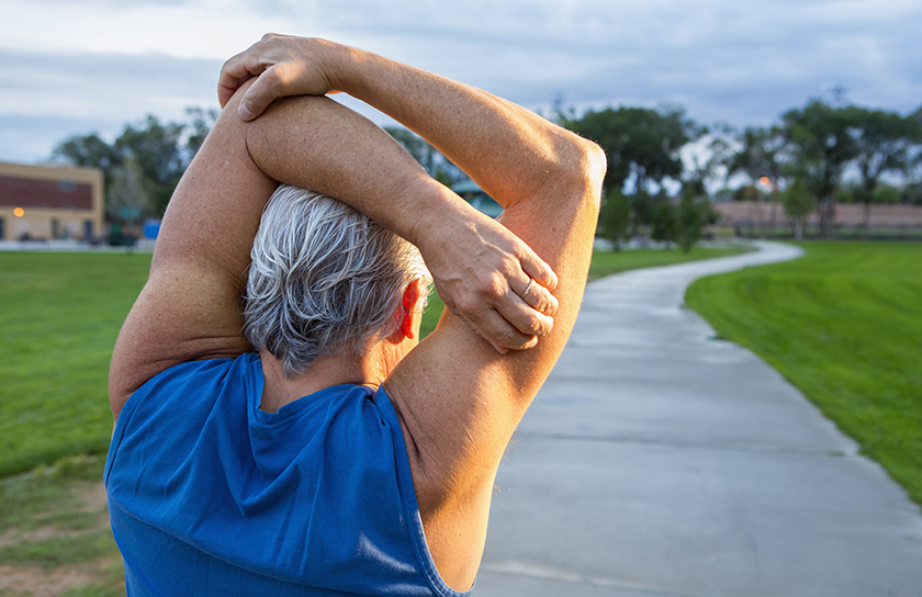 older male stretching before a run in the park