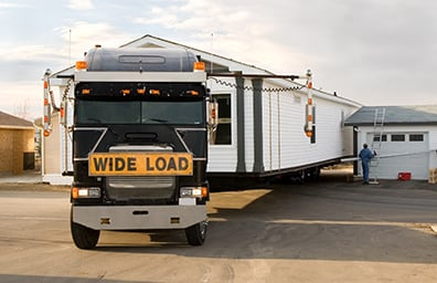 truck hauling mobile home with wide load sign