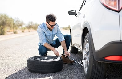 young man on side of road fixing flat tire