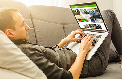 young man shopping for car online laying down in couch